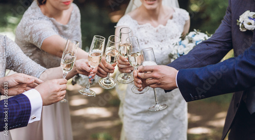 Foto op Canvas Alcohol happy group of people toasting with champagne. hands holding glasses of champagne and clinking. bride bridesmaids and groom groomsmen having fun. holiday celebration. christmas feast