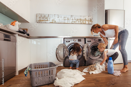 Obraz na plátne Family doing laundry together at home