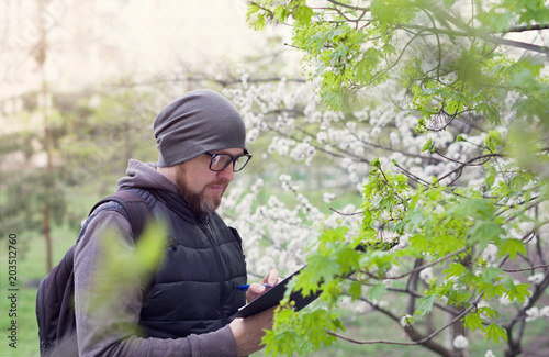 Valokuva  Man ecologist conducts research during the flowering of trees