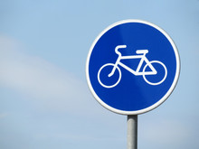 Bicycle Road Sign Isolated On Blue Sky. White Bicycle Symbol On The Blue Circle Of Sign