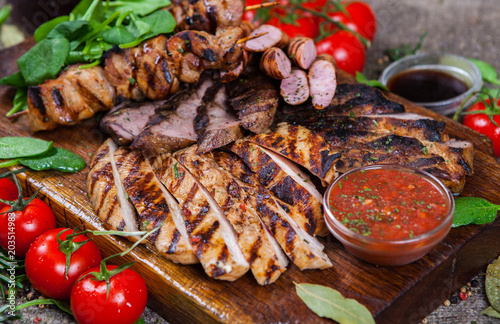 In de dag Grill / Barbecue Mixed grilled meat platter. Assorted delicious grilled meat with vegetable. Mixed grilled meat with pepper sauce and vegetables.