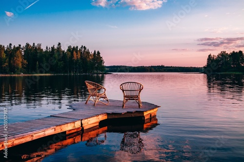 Photo Two wooden chairs on a wood pier overlooking a lake at sunset