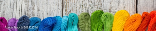 Fotografie, Obraz Banner of colorful sewing threads for embroidery on white wooden background