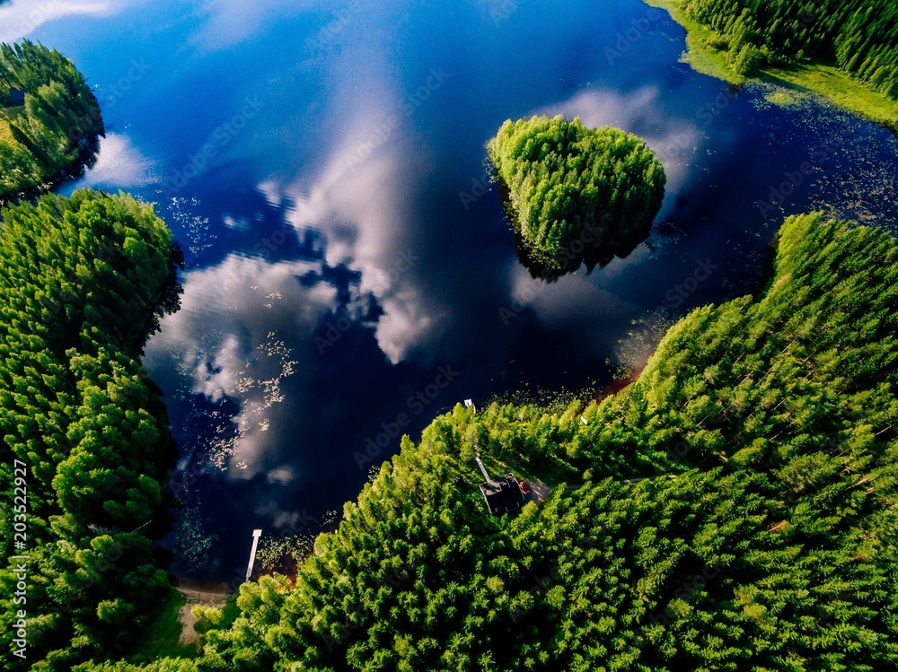 Aerial view of blue lake with island and green forests on a sunny summer day in Finland.