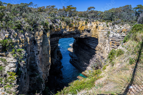 Deurstickers Zwart Tasman Peninsula, Tasmania, Australia: Scenic coastline of rocky cliff Tasman arch with old stone formations dramatic structures near blue wild ocean perfect hiking landscape countryside Port Arthur