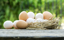 Group Of Raw  Eggs In Straw On Wooden Table With Soft Light Of Nature On Background.