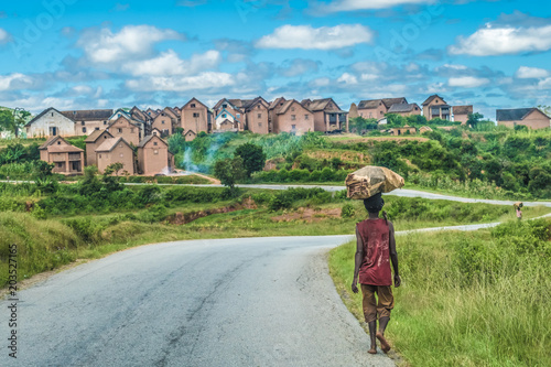 Tuinposter Zalm Mostly barefooted villagers walk long distances to bring their produce for sale in weekly regional markets, National Route 7 South of Tananarivo, Madagascar