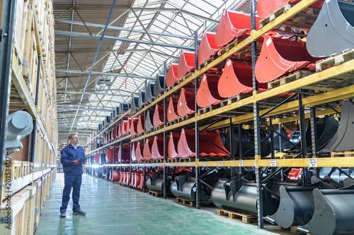 Worker in storage space in engineering factory