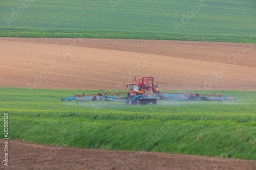 Foto op Canvas Zalm Spring chemical treatment of cereals with red tractor
