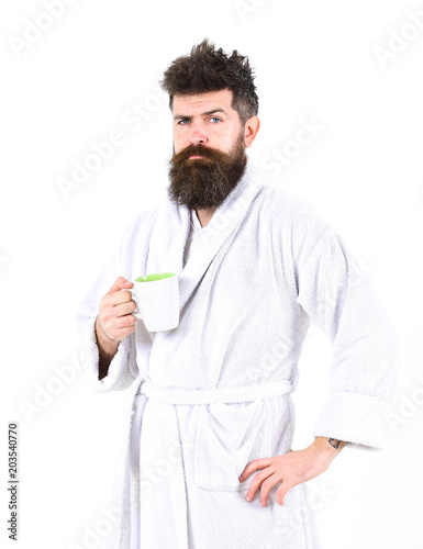 Obraz na plátně  Man with beard and disheveled hair stands in bathrobe, holds mug with tea or coffee, white background