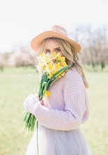 A Young Beautiful Blonde Girl In A Hat And A Lush Long Skirt With Bouquets Of Daffodils In The Spring Garden. Young Lady Holding Bouquet Of Daffodils In Spring