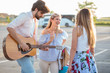 Group of young tourists having fun in a parking lot. Man playing guitar and entertaining his two female friends.