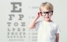 Little Boy In Glasses Having Eye Test, Over Eye Chart. Tables Vision Testing. Visiting A Doctor Pediatric Ophthalmologist.