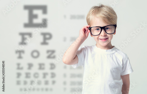 Little boy in glasses having eye test. Tables vision testing. Visiting a doctor pediatric ophthalmologist.