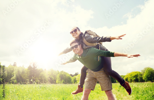 Foto op Aluminium Voetbal travel, hiking, backpacking, tourism and people concept - happy couple with backpacks having fun and walking along country road outdoors