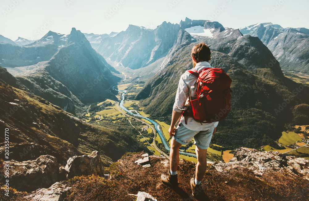 Fototapety, obrazy: Hiking alone in Norway mountains Man with red backpack enjoying landscape on cliff solo traveling healthy lifestyle concept active summer vacations