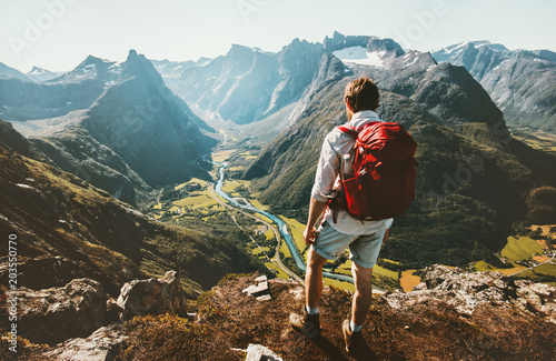 Montage in der Fensternische Schokobraun Hiking alone in Norway mountains Man with red backpack enjoying landscape on cliff solo traveling healthy lifestyle concept active summer vacations