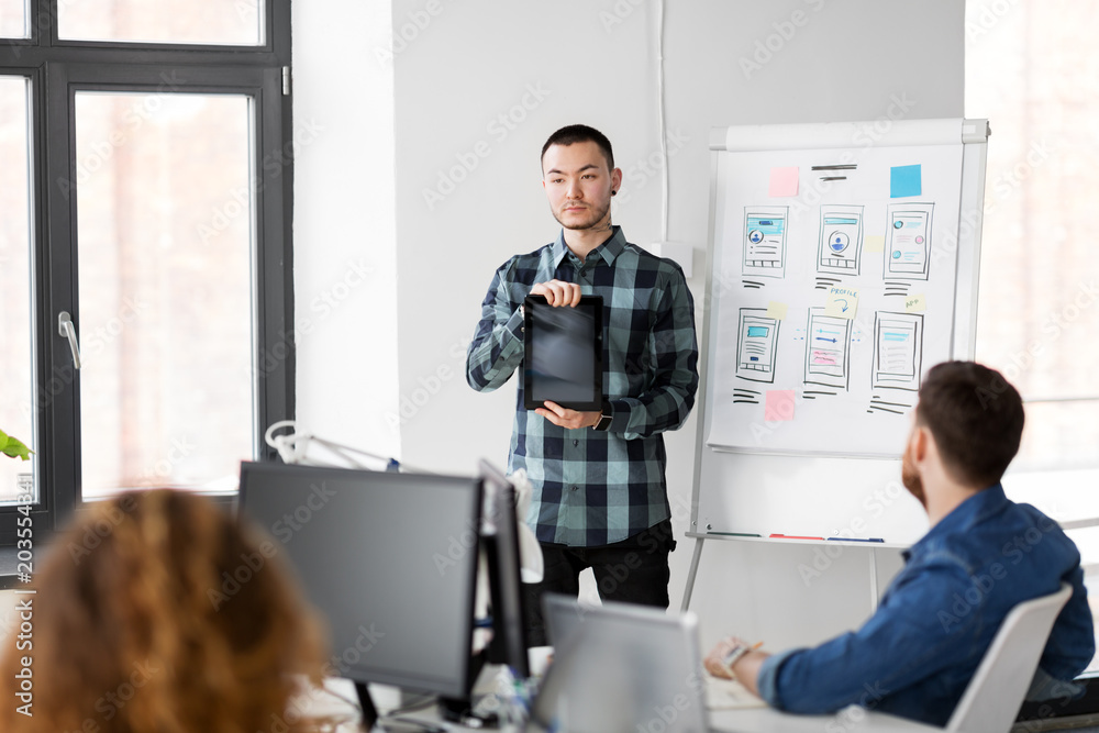business, technology and people concept - man showing tablet pc computer to creative team at office presentation