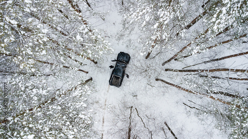 Photo  Aerial view on SUV 6x6 that rides by winter road in snow-covered forest