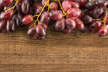 Red Globe Grapes Table Top Isolated On Brown Wood Background Shiny Deep Pink Berries.
