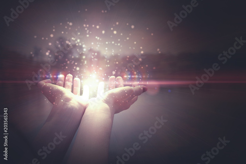 Photo  Hands holding magic particles