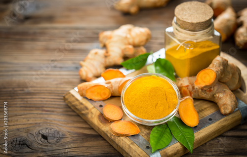 Poster Aromatische Turmeric powder and turmeric roots on the wooden table