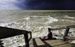 Hombre joven sentado en el muelle de madera frente al mar en