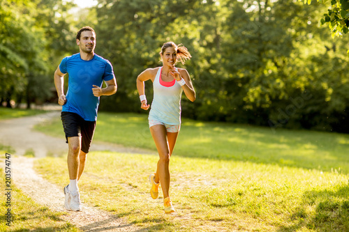 Poster Jogging Young couple running in the park on a sunny day