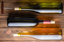 Three Bottles Of Wine Against Wooden Background