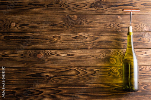 Fotografia, Obraz  Bottle of white wine with corkscrew on wood
