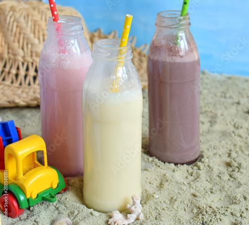 Foto op Aluminium Milkshake Three bottle of various milkshakes (chocolate, strawberry and vanilla). Healthy smoothie with straw. Tasty milk shake cocktails. Refreshing summer drink on yellow sand summer beach. Copy space