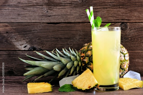 Glass of pineapple juice. Side view on a rustic wood background,