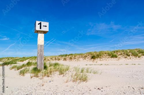 Fotografie, Obraz Beach post on sand against blue sky, IJmuiden, Netherlands