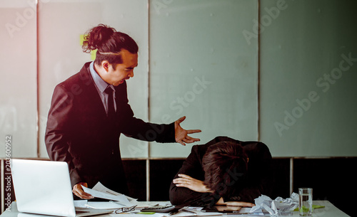 Photo  A boss angry because sees a worker sleeping in the office.