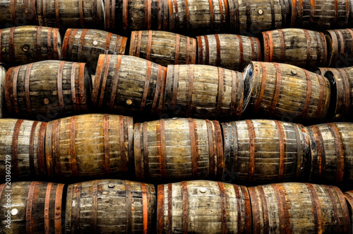 Leinwand Poster Stacked pile of old whisky and wine wooden barrels