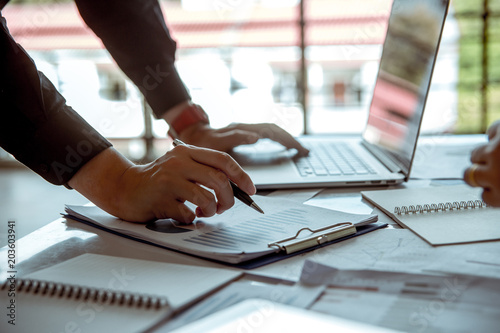 Fototapety, obrazy: Businessman holding a pen writing financial reports papers, and uses a notebook computer along the way.