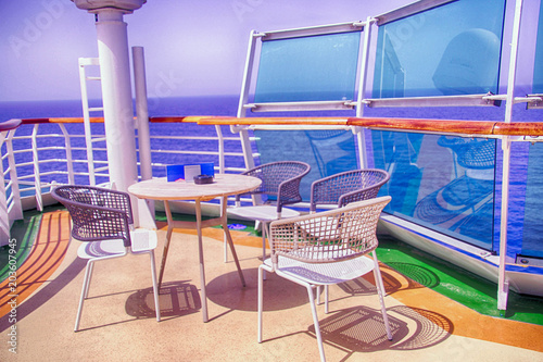 Photo  Table and chairs on outside deck on a cruise ship