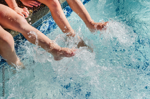Children's feet splashing in sparkling blue pool water. Fun and play in this outdoor summertime activity.