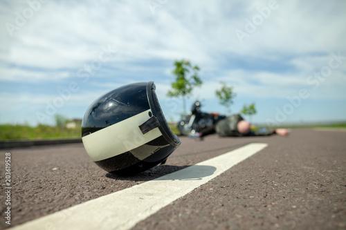 Fotografie, Obraz  biker helmet lies on street near a motorcycle accident