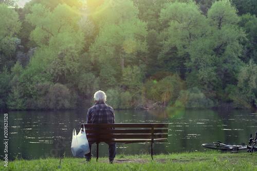 Montage in der Fensternische Olivgrun Old man sitting on bench near river and watching sunset. Senior man sitting alone in park.