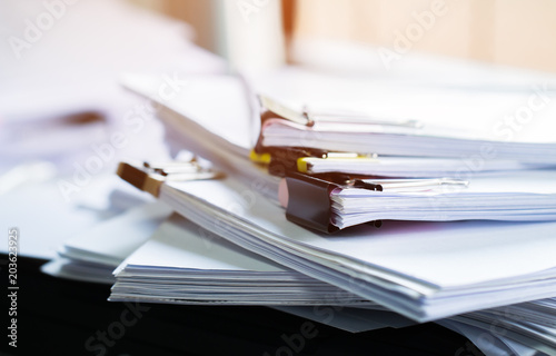 Fotomural  Stack of papers documents in archives files with clip papers on table at offices,  Busy offices and Pile of data unfinished folders on office desk indoor near window,  Business concept