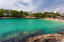 Cala Gran Beach With Turquoise Water Crowded With Tourists In Mallorca, Spain