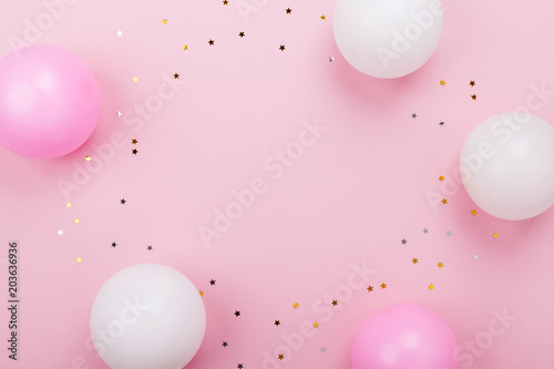 Pastel pink table with balloons and confetti for birthday top view. Flat lay composition.