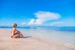 Female lying on a sandy beach near the ocean / sea water.