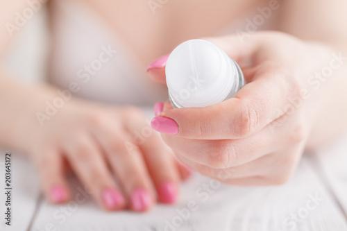 Photo Female hand with antiperspirant bottle