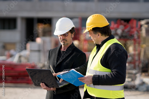 Civil engineer giving instructions to a construction worker using a computer laptop. Outdoors