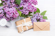 Lilac flowres, gift box and envelope on white wooden background. Retro style. Holiday composition, copy space