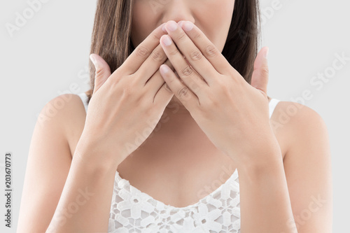 Asian woman use both hands close mouth for not commenting or refusing on gray ba Canvas Print