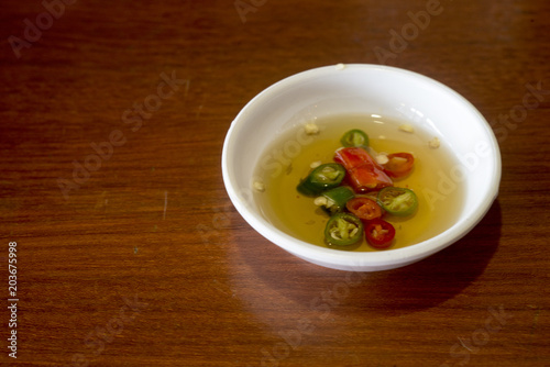 Pepper sauce in a white cup on a wooden table