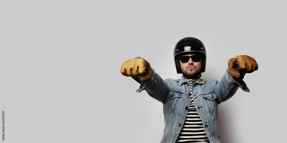 Fototapeta Young biker in a blue denim jacket pretending to ride a motorcycle isolated on white background. Horizontal. Wide